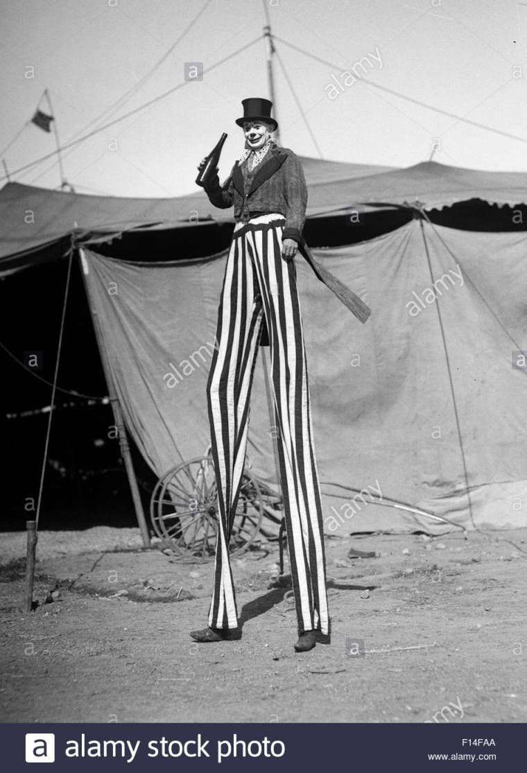 1930s-circus-performer-smiling-clown-on-stilts-striped-pants-looking-F14FAA